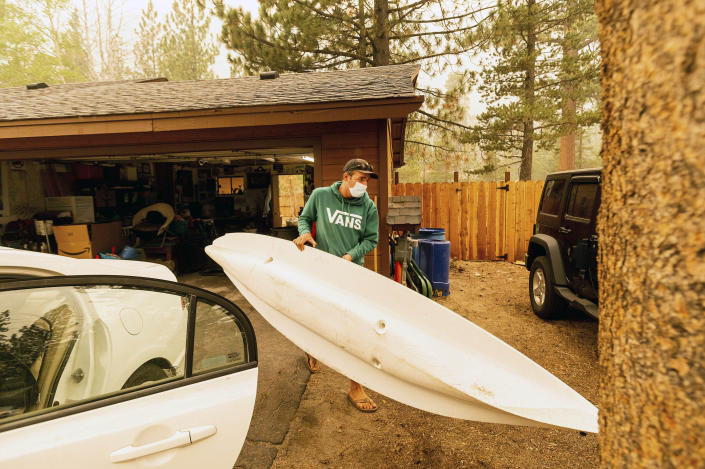 As the Caldor Fire approaches, Greg Collard carries a kayak while helping family members evacuate from their South Lake Tahoe, Calif. home on Friday, Aug. 27, 2021. (AP Photo/Noah Berger)