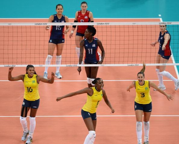 (L-R foreground) Brazil's Fernanda Rodrigues, Fabiana Claudino and Danielle Lins celebrate during the women's volleyball gold medal match of the London 2012 Olympics Games against the US, in London on August 11, 2012. AFP PHOTO / FRANCISCO LEONG (Photo credit should read FRANCISCO LEONG/AFP/GettyImages)
