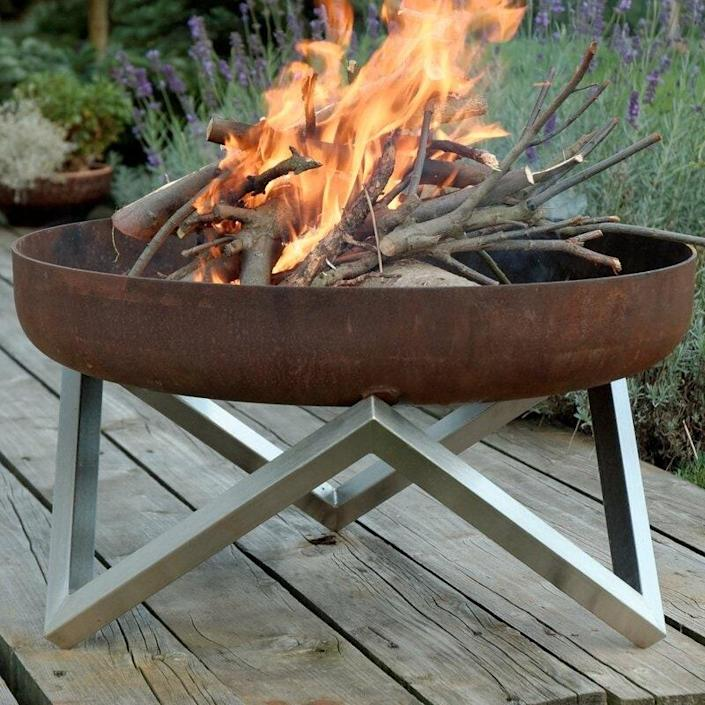 """We love the contrast between the rust patina on the bowl and the silver on the legs of this modern fire pit. This wood-burning vessel will definitely level up your outdoor decor. $369, Wayfair. <a href=""""https://www.wayfair.com/Orren-Ellis--Faisal-Stainless-Steel-Wood-Burning-Fire-Pit-X113779808-L327-K~W002668797.html"""" rel=""""nofollow noopener"""" target=""""_blank"""" data-ylk=""""slk:Get it now!"""" class=""""link rapid-noclick-resp"""">Get it now!</a>"""