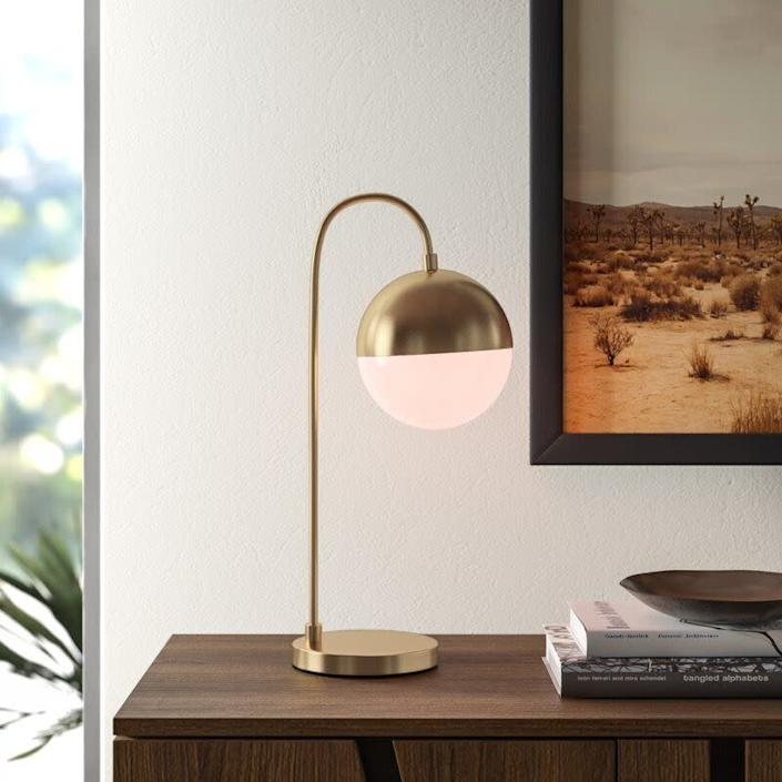 """This modern lamp is perfect for those who aren't traditionalists. It features a white acrylic globe shade, round pedestal base and arched arm. And this lamp comes with a 25-watt compact fluorescent bulb. <a href=""""https://fave.co/2RrwhBl"""" rel=""""nofollow noopener"""" target=""""_blank"""" data-ylk=""""slk:Find it for $78 at AllModern"""" class=""""link rapid-noclick-resp""""> Find it for $78 at AllModern</a>."""
