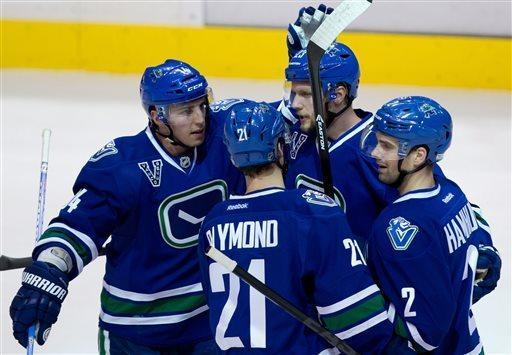 Vancouver Canucks' Alex Burrows, from left, Mason Raymond, Alexander Edler, of Sweden, and Dan Hamhuis celebrate Edler's goal against the Detroit Red Wings during the first period of an NHL hockey game in Vancouver, British Columbia, on Saturday April 20, 2013. (AP Photo/The Canadian Press, Darryl Dyck)