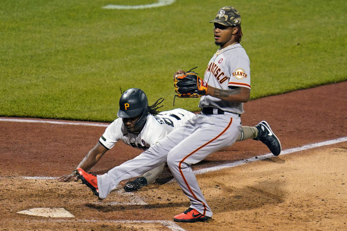Pittsburgh Pirates' Troy Stokes Jr., rear, scores on a wild pitch by San Francisco Giants relief pitcher Camilo Doval, right, during the seventh inning of a baseball game in Pittsburgh, Saturday, May 15, 2021. (AP Photo/Gene J. Puskar)