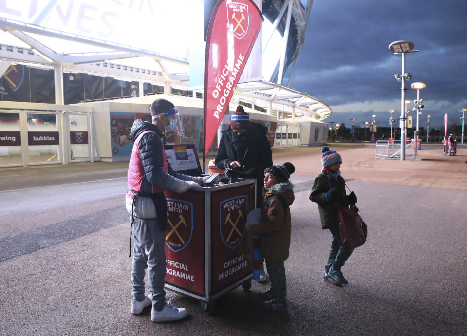 West Ham fans buy a programme ahead of the English Premier League soccer match between West Ham United and Manchester United at the London stadium in London, England, Saturday, Dec. 5, 2020. (Adam Davy / Pool via AP)