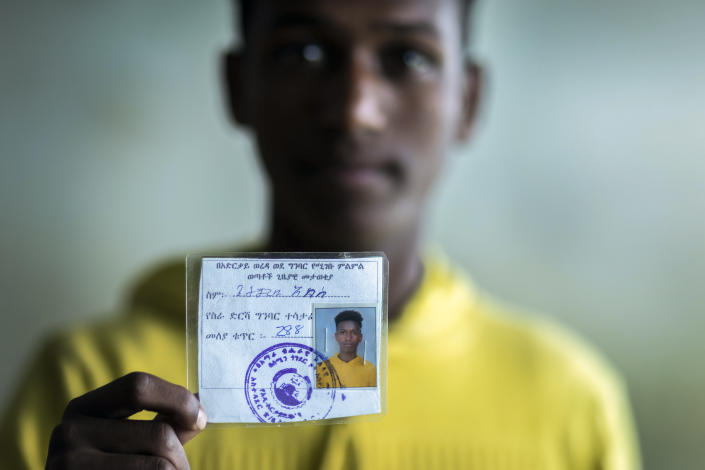 Getachew Abebe, 20 years old, holds his temporary identity card indicating he has chosen to participate at the front line of the conflict, at a center for the internally-displaced in Debark, in the Amhara region of northern Ethiopia Friday, Aug. 27, 2021. Abebe fled his hometown of Addi Arkay when Tigrayan fighters took it over and he is now finalizing basic training so that he can fight with the Fano Youth Liberation Movement militia. (AP Photo/Mulugeta Ayene)