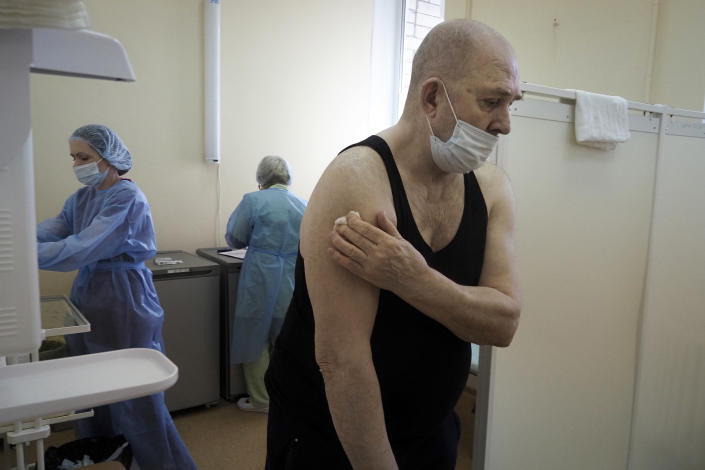 An elderly man leaves a room after getting a shot of Russia's Sputnik V coronavirus vaccine in the clinic in Petrozavodsk, Karelia region, Russia, Monday, Feb. 15, 2021. Russia took pride in being the first country to approve a coronavirus vaccine, although it faced criticism from aboard for doing it before completing the advanced testing necessary to ensure Sputnik V's safety and effectiveness. (AP Photo/Dmitri Lovetsky)