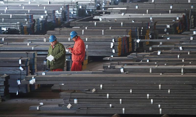 FILE PHOTO: Workers check steel bars at a factory of Dongbei Special Steel Group Co., Ltd. in Dalian