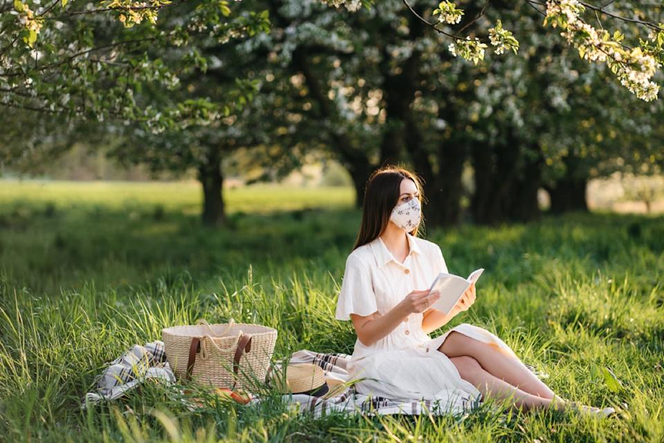 white woman with a face mask reading a book next to a picnic basket on a blanket