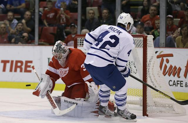 Detroit Red Wings goalie Jimmy Howard (35) deflects a shot by Toronto Maple Leafs center Tyler Bozak (42) during the first period of an NHL hockey game in Detroit, Friday, Sept. 27, 2013. (AP Photo/Carlos Osorio)