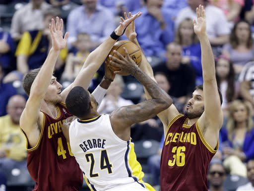 Cleveland Cavaliers center Tyler Zeller, left, and forward Omri Casspi, right, team up to block the shot of Indiana Pacers forward Paul George in the first half of an NBA basketball game in Indianapolis, Tuesday, April 9, 2013. (AP Photo/Michael Conroy)