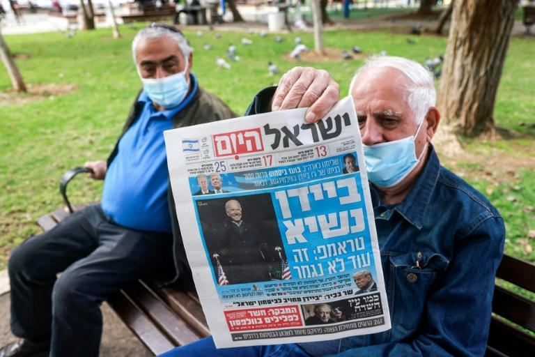 A man holds up a copy of Israeli newspaper Israel Hayom