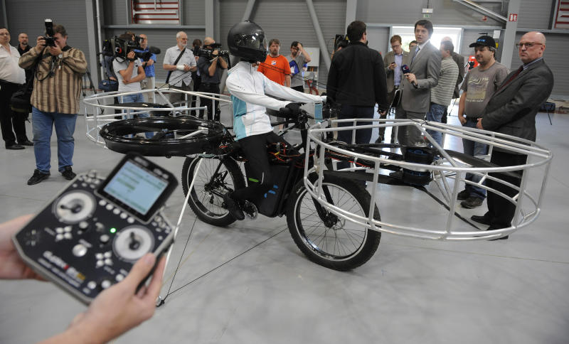 Journalists watch the remote-controlled Flying Bike with a test dummy during its presentation in Prague on Wednesday, June 12, 2013. Three Czech companies have teamed up to make a prototype of an electric bicycle that can fly. Controlled remotely, the bike carrying a figurine successfully took off Wednesday inside a large exhibition hall in Prague and landed safely after a five-minute flight. (AP Photo/CTK, Stanislav Zbynek) SLOVAKIA OUT