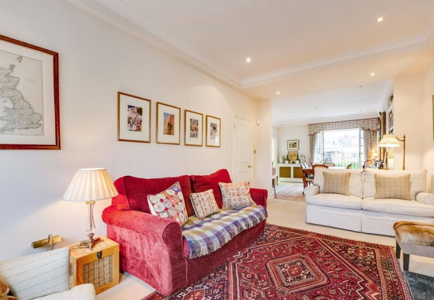 Red sofas and printed rugs add a pop of colour to the reception room (Right Move)