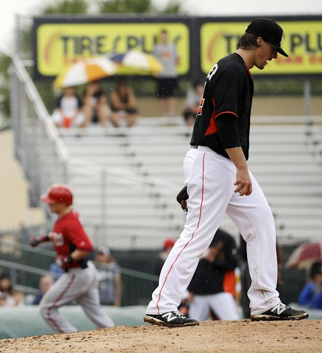 Miami Marlins starting pitcher Tom Koehler, right, stands on the mound after giving up a home run to Washington Nationals' Nate McLouth, left, in the sixth inning of an exhibition spring training baseball game, Monday, March 24, 2014, in Jupiter, Fla. (AP Photo/David Goldman)
