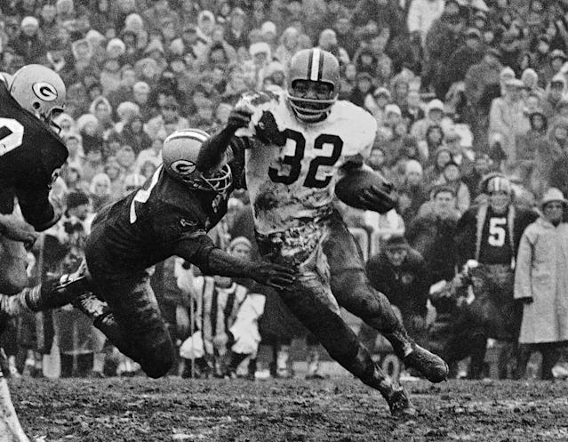 FILE - In this Jan. 2, 1966, file photo, Cleveland fullback Jim Brown (32) turns the corner as a Green Bay Packer defender swings with him in Green Bay, Wisc. Long before quarterbacks took center stage, the NFL was a running backs league. From Red Grange to Jim Brown to O.J. Simpson to Walter Payton to Emmitt Smith, the workhorse back has been a symbol of toughness and perseverance. (AP Photo/File)