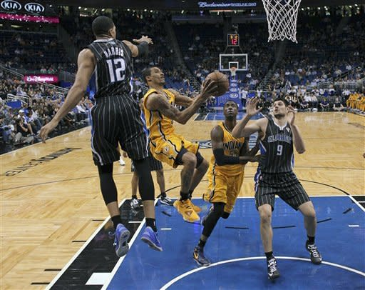 Indiana Pacers' George Hill, center left, gets between Orlando Magic's Tobias Harris (12) and Nikola Vucevic (9) for a shot during the first half of an NBA basketball game, Friday, March 8, 2013, in Orlando, Fla. (AP Photo/John Raoux)