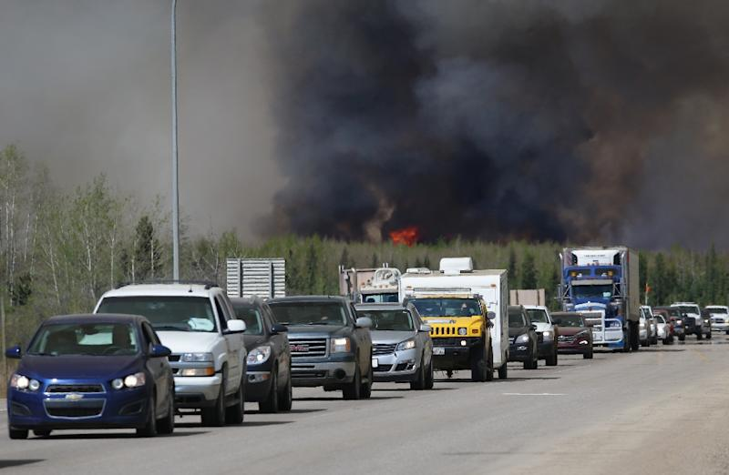 A convoy of evacuees drives south as flames and smoke rises along the highway near near Fort McMurray, Alberta on May 6, 2016 (AFP Photo/Cole Burston/)
