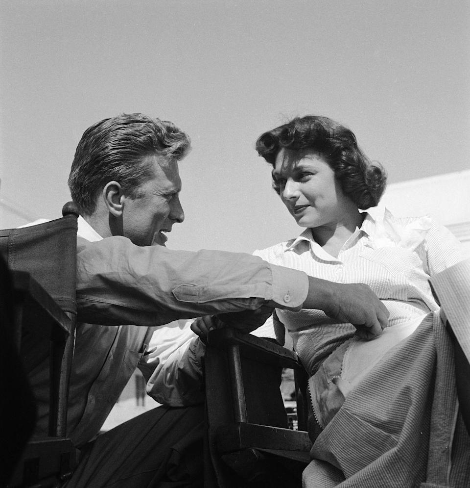 <p>On the set of <em>Champion, </em>Douglas discusses a scene with his costar actress Ruth roman.</p>