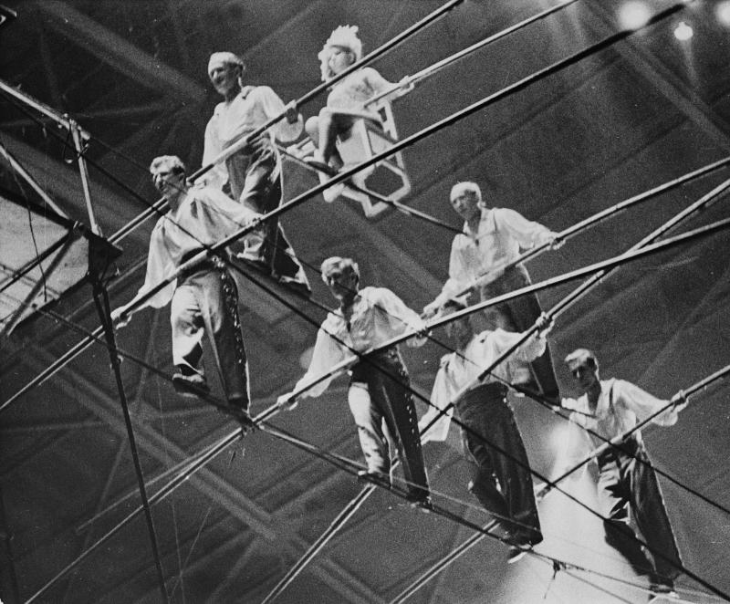 "FILE- In this Jan. 30, 1962 file photo, the Great Wallendas walk the high wire during their three-tier seven-person pyramid performance at the State Fair Coliseum in Detroit, Michigan. During the performance the pyramid formation collapsed and the performers fell to the ground injuring performers Jana Schepp and Mario Wallenda, as well as killing performers Richard Faughnan and Dieter Schepp. From left to right, bottom row, are, Dieter Schepp; Mario Wallenda; Richard Faughnan and Gunther Wallenda. From left ro right in the second row are Karl Wallenda and Herman Wallenda. Sitting on chair is Jana Schepp. On Friday, June 15, 2012, Karl's great grandson, Nick Wallenda, will attempt a high wire walk over Niagara Falls on live television, hoping to write his famous family's name into the 153-year-old legend of daredevils who've ""conquered"" the natural wonder. (AP Photo, File)"