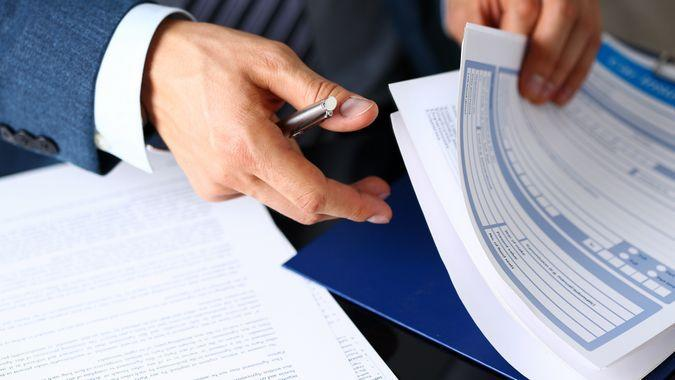 Male arm in suit offer insurance form clipped to pad and silver pen to sign closeup.
