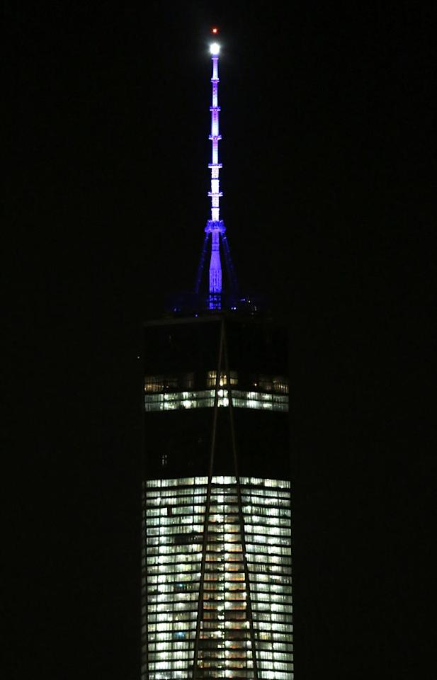 The beacon and spire of One World Trade Center are lit up, as seen from The Heights neighborhood of Jersey City, N.J., Friday, Nov. 8, 2013. The Port Authority of New York and New Jersey, who tested the lights on Friday, said the beacon is packed with nearly 300 modules and their glow can be seen for up to 50 miles. The beacon and spire together stand 408 feet tall and bring the building, formerly called the Freedom Tower, to its symbolic height of 1,776 feet. The Durst Organization operates the spire, which will serve broadcasters. (AP Photo/Julio Cortez)