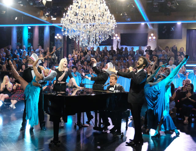 """This Sept. 26, 2018 image released by CBS shows Sophie Turner, left, and Josh Groban, right, performing """"Baby Shark"""" with host James Corden on """"The Late Late Show with James Corden,"""" in Los Angeles. The viral kid music video """"Baby Shark"""" has taken a big bite out of the culture worldwide, and there's more to come for Christmas. New toys tied to the snappy song sold out in pre-sale ahead of the holiday on Amazon, with third-party sellers jacking up the prices to $100 and more. Celebrities have hopped on board with their own versions of the song and dance, complete with all the shark hand gestures. (Jason LaVeris /CBS via AP)"""
