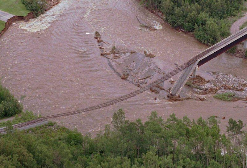 <p>Train tracks are seen hanging over a river near La Baie, Que., on July 21, 1996, as floods destroyed the bridge that held up the tracks. Millions of dollars worth of damage was reported during the Saguenay floods. </p>