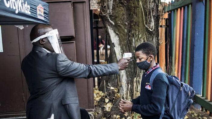On the  same day a child in the South African city of Johannesburg gets his temperature checked as the country eases its lockdown restrictions.