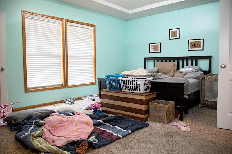 disorganized dated bedroom with blue walls