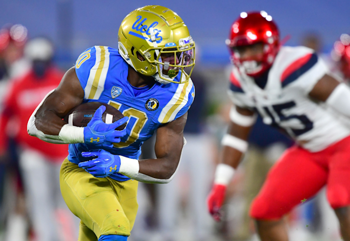 UCLA running back Demetric Felton carries the ball for a gain in the first half against Arizona on Nov. 28, 2020.