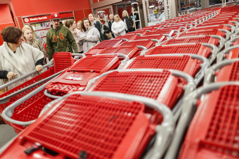 "FILE - In this Nov. 23, 2018, file photo shoppers enter and take their shopping carts during a Black Friday sale at a Target store in Newport, Ky. Target is launching a private food label next month as it attempts to energize grocery sales. On Sept. 15, 2019, 650 products will appear on store shelves under the brand ""Good & Gather."" (AP Photo/John Minchillo, File)"