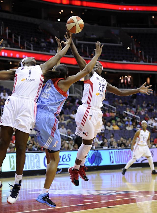 Washington Mystics guard Matee Ajavon, right, and Crystal Langhorne (1) battle for the ball against Atlanta Dream guard Tiffany Hayes during the first half of Game 2 of the WNBA basketball Eastern Conference semifinal series, Saturday, Sept. 21, 2013, in Washington. (AP Photo/Nick Wass)