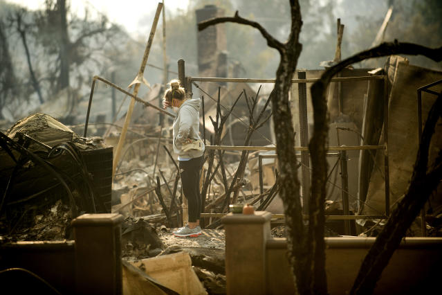 <p>Bree Laubacher pauses while sifting through rubble at her Ventura, Calif., home following a wildfire on Wednesday, Dec. 6, 2017. A barbecue smoker and her son's batting cage survived the blaze. (Photo: Noah Berger/AP) </p>