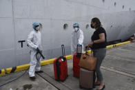 A healthcare worker disinfects the luggage of an evacuee before boarding the Royal Caribbean cruise ship Reflection, in Kingstown, on the eastern Caribbean island of St. Vincent, Friday, April 16, 2021. La Soufriere volcano has shot out another explosive burst of gas and ash Friday morning as the cruise ship arrived to evacuate some of the foreigners who had been stuck on a St. Vincent island by a week of violent eruptions. (AP Photo/Orvil Samuel)