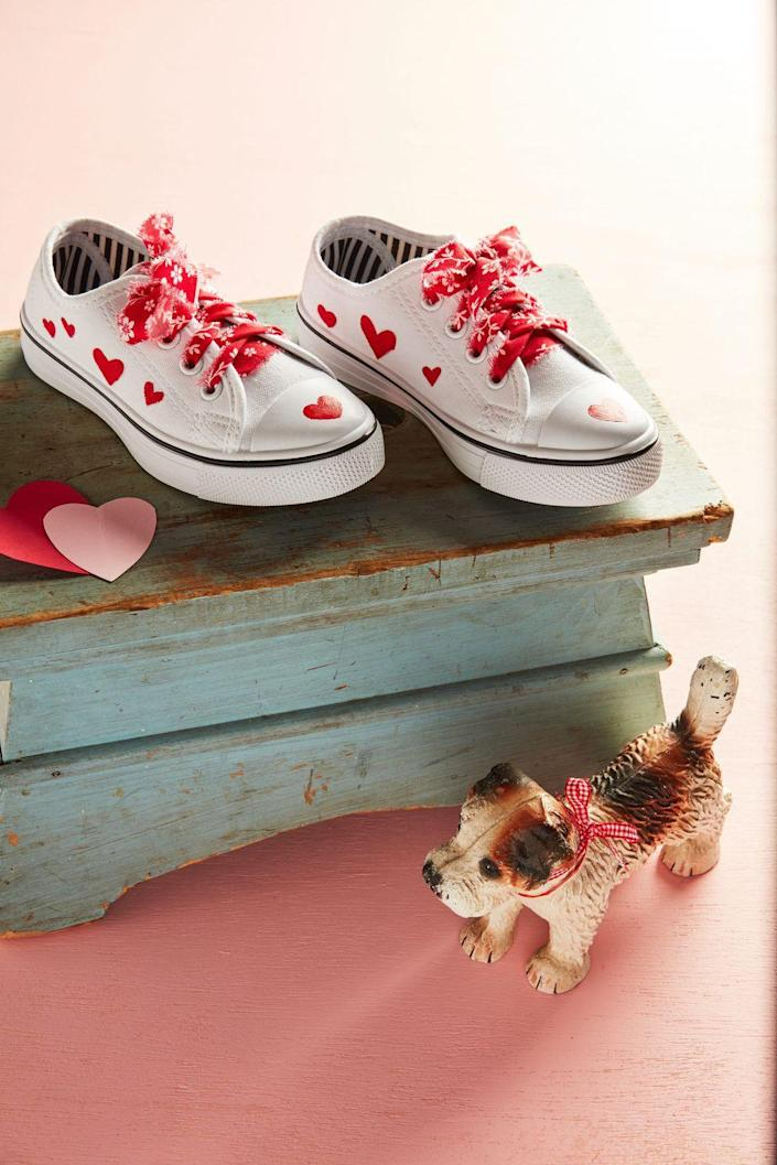 """<p>Kids will strut their stuff this Valentine's Day in DIY decorated sneakers with colorful fabric laces.</p><p><strong>To make:</strong> Use fabric paint to paint hearts on the top and sides of sneakers. Tear a long piece of fabric into thin strips and thread through eyelets. </p><p><a class=""""link rapid-noclick-resp"""" href=""""https://www.amazon.com/Jacquard-Products-Textile-Fabric-2-25-Ounce/dp/B0006IK268/ref=sr_1_3?tag=syn-yahoo-20&ascsubtag=%5Bartid%7C10050.g.1584%5Bsrc%7Cyahoo-us"""" rel=""""nofollow noopener"""" target=""""_blank"""" data-ylk=""""slk:SHOP FABRIC PAINT"""">SHOP FABRIC PAINT</a></p>"""