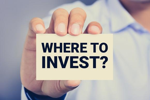 """person holding up a card that says """"where to invest?"""""""