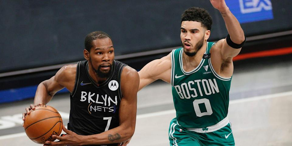 Kevin Durant drives past Jayson Tatum during a game.