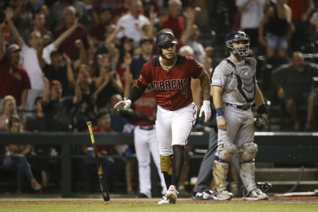 Arizona Diamondbacks' Ketel Marte watches his grand slam, near San Diego Padres catcher Austin Hedges during the seventh inning of a baseball game Wednesday, Sept. 4, 2019, in Phoenix. (AP Photo/Ross D. Franklin)