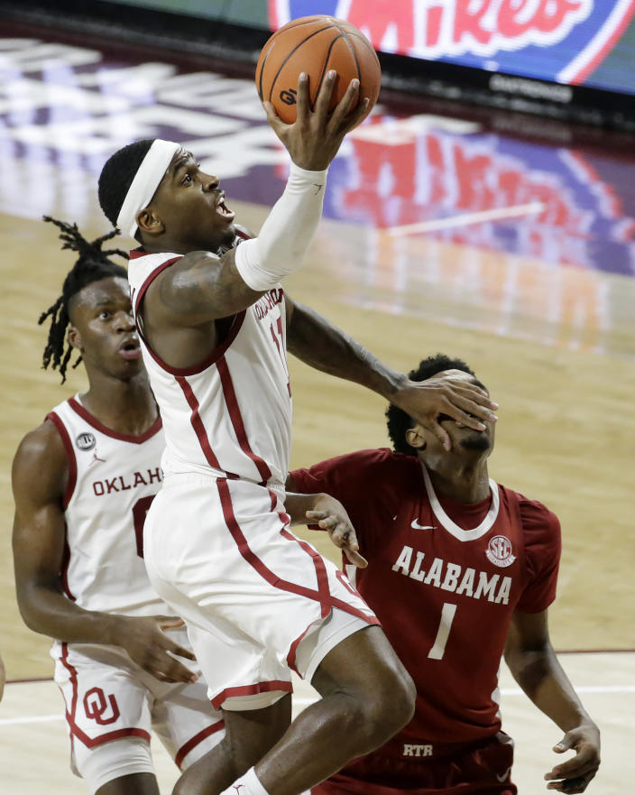 Oklahoma's De'Vion Harmon (11) takes a shot against Alabama's Herbert Jones (1) as Oklahoma's Victor Iwuakor (0) looks on during the second half of an NCAA college basketball game in Norman, Okla., Saturday, Jan. 30, 2021. (AP Photo/Garett Fisbeck)