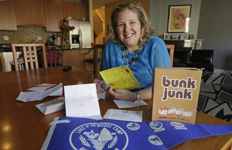 This May 15, 2013 photo shows Lauren Russ in Chicago, posing with letters that she wrote home as a child from sleepaway camp begging her parents to come and get her. While many children enjoy attending overnight camp, Russ is one of a number of adults who look back on the experience with less-than-fond memories of feeling homesick and lonely. Russ' tearful letters home to mom and dad are so famous in her family that her parents even read them at her wedding shower 10 years ago. (AP Photo/Michael S. Green)