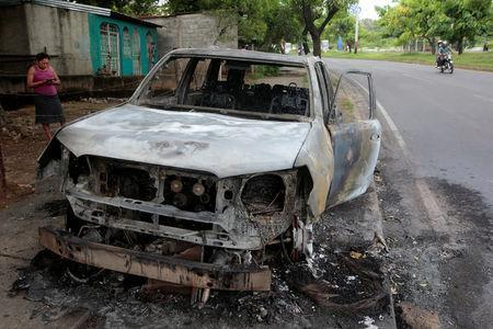 A woman stands next to a burned car after a protest against Nicaraguan President Daniel Ortega's government in Managua, Nicaragua May 31, 2018.REUTERS/Oswaldo Rivas