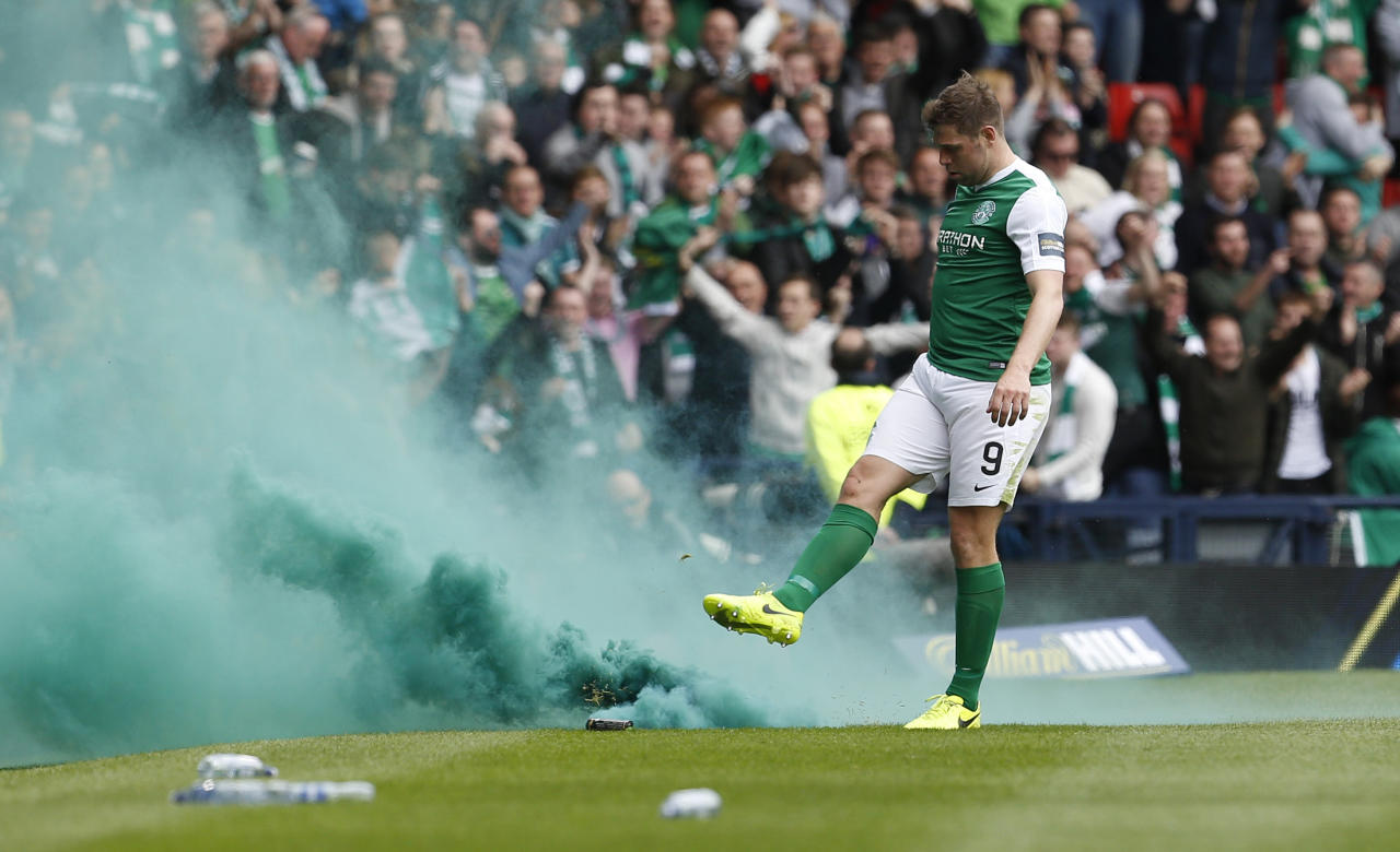 "Britain Soccer Football - Hibernian v Aberdeen - Scottish Cup Semi Final - Hampden Park, Glasgow, Scotland - 22/4/17 Hibernian's Grant Holt kicks a smoke bomb off the pitch Action Images via Reuters / Craig Brough Livepic EDITORIAL USE ONLY. No use with unauthorized audio, video, data, fixture lists, club/league logos or ""live"" services. Online in-match use limited to 45 images, no video emulation. No use in betting, games or single club/league/player publications.  Please contact your account representative for further details."