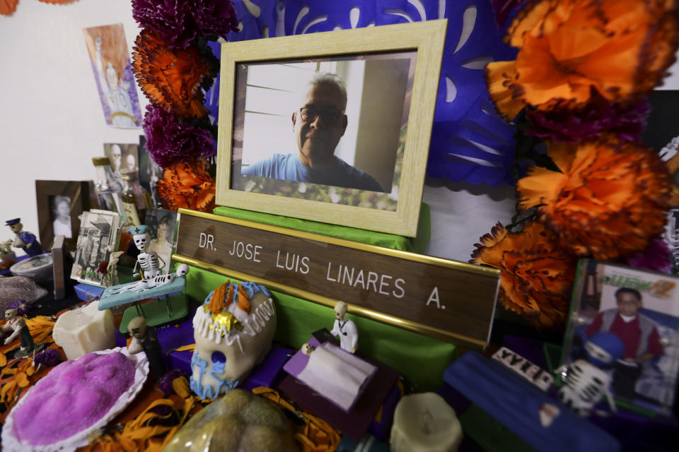 A portrait of Dr. Jose Luis Linares who died from symptoms related to COVID-19, placed on a Day of the Dead altar made by his wife Rosario Martinez at their home in Mexico City, Sunday, Nov. 1, 2020. He is one of more than 1,700 Mexican health workers officially known to have died of COVID-19 who are behind honored with three days of national mourning on these Days of the Dead. (AP Photo/Eduardo Verdugo)