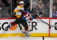 Colorado Avalanche center Nathan MacKinnon (29) checks Nashville Predators left wing Filip Forsberg (9) into the boards during the first period in Game 6 of an NHL hockey first-round playoff series Sunday, April 22, 2018, in Denver. (AP Photo/Jack Dempsey)