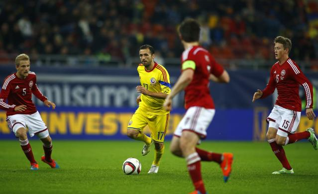 Romania's Lucian Sanmartean (C) is challenged by Denmark's Nicolai Boilsen (L), Nicolaj Thomsen (R) and William Kvist Jorgensen during their international friendly soccer match at National Arena in Bucharest November 18, 2014. Romania have reaped the rewards of a rejuvenated Sanmartean after the veteran returned following a three-year break to become instrumental in guiding the team to the top of their Euro 2016 qualifying group. The 34-year-old midfielder was named in Romania's starting lineup for the eagerly-anticipated clash with neighbours Hungary last month, his first international appearance since playing 28 minutes of a Euro 2012 qualifier against Belarus on October 7, 2011. REUTERS/Bogdan Cristel (ROMANIA - Tags: SPORT SOCCER)