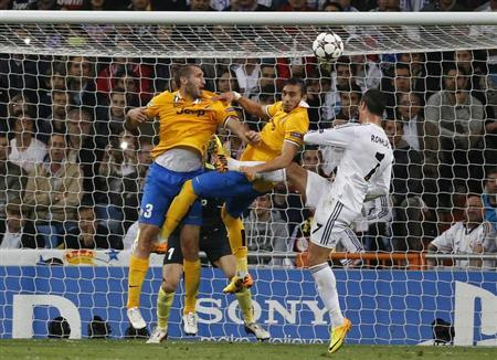 Real Madrid's Cristiano Ronaldo (R) heads the ball over Juventus' Martin Caceres (C) and Giorgio Chiellini during their Champions League soccer match at Santiago Bernabeu stadium in Madrid October 23, 2013. REUTERS/Paul Hanna