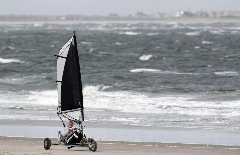 A person rides in a cart blown by the winds along the Altlantic Ocean in North Wildwood, N.J., Saturday, Oct. 27, 2012, as the winds pick up ahead of Hurricane Sandy. From the lowest lying areas of the Jersey shore, where residents were already being encouraged to leave, to the state's northern highlands, where sandbags were being filled and cars moved into parking lots on high ground, New Jersey began preparing in earnest for Hurricane Sandy. (AP Photo/Mel Evans)