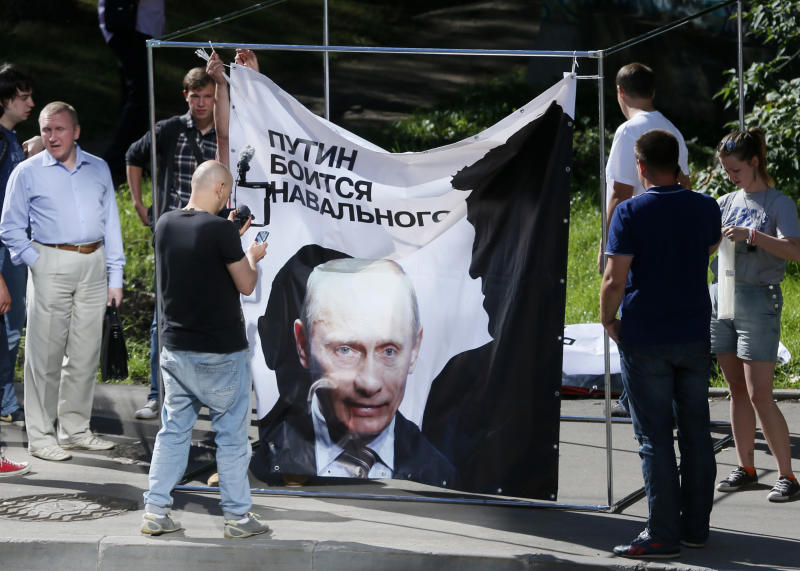 """Russian opposition leader Alexei Navalny's supporters stay outside a court in Kirov, Russia early Friday, July 19, 2013. Navalny, a charismatic and creative Russian opposition leader who exposed high-level corruption and mocked the Kremlin, was sentenced to five years in prison for embezzlement on Thursday, in a verdict that set off street protests and drew condemnation from the West. The poster at the background reads """"Putin is afraid of Navalny."""" (AP Photo/Dmitry Lovetsky)"""