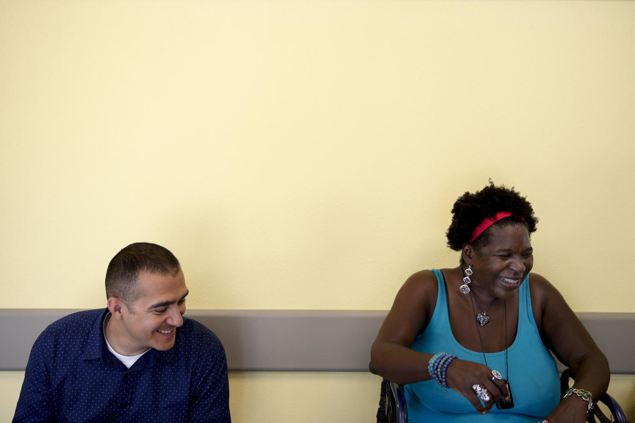 "In a Monday, July 16, 2018 photo, Virta Woodard, a 56-year-old diabetic, right, and her care manager, Armando Contreras, share a light moment while waiting for a ride after a brief exercise at a gym in Lakewood, Calif. Woodard gets weekly phone calls from her care manager, and she's started hitting Nifty After Fifty fitness centers since she signed up for a program called ""Togetherness"" covered by the Blue Cross-Blue Shield insurer Anthem Inc. The health care system is becoming more focused on keeping patients healthy instead of waiting to treat them once they become sick or wind up in the hospital. The 56-year-old diabetic lives with daily pain due to her disease and a injuries from a car accident, but she's lost 34 pounds since joining the program. (AP Photo/Jae C. Hong)"