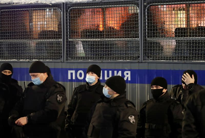 Law enforcement officers stand next to a police van during a rally to protest the detainment of Russian opposition leader Navalny, in Saint Petersburg