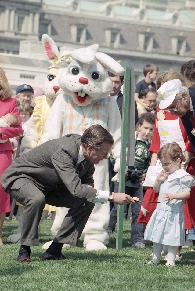 <p>President George H.W. Bush bends down and gives his granddaughter, Ellie LeBlond, instructions on how to roll an egg at the lllth annual Easter Egg Roll that took place, Monday, March 27, 1989 on the South Lawn of the White House in Washington. (Photo: Dob Daugherty/AP) </p>